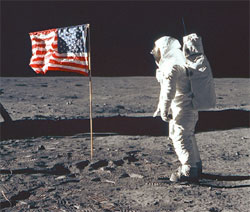 Astronaut Edwin E. Aldrin Jr., lunar module pilot of the first lunar landing mission, poses for a photograph beside the deployed United States flag during an Apollo 11 extravehicular activity (EVA) on the lunar surface on July 20, 1969.