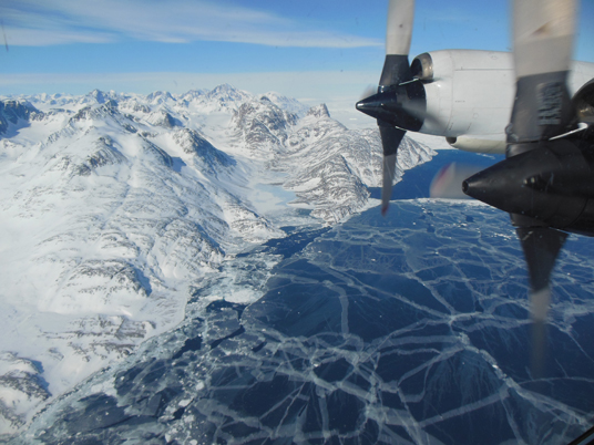 The plane flies over sea ice. The P-3B propeller can be seen out the window of the plane. Credit: Christy Hansen