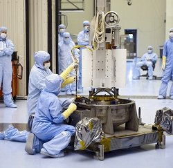 Clean-suited technicians assemble a TE generator for a spacecraft. NASA's expertise in this technology can help cars and trucks to run more efficiently.