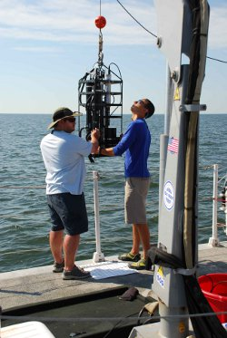 Scientists used multiple instruments to measure water quality. Here, members of the team deploy a package of instruments that take measurements of light interacting with particles in the water. Photo courtesy of Maria Tzortziou