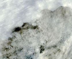 Thick cloud cover briefly fell away to reveal this first image of icebergs breaking away from the Sulzberger Ice Shelf due to sea swell from the Tohoku Tsunami, which had originated 8,000 miles away about 18 hours earlier. The icebergs can be seen behind a thin layer of clouds just off the ice shelf near the center of the image. Source: MODIS Rapid Response/NASA.