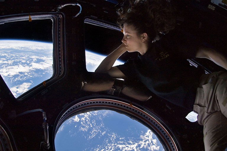 NASA astronaut Tracy Caldwell Dyson, Expedition 24 flight engineer, looks through a window in the Cupola of the International Space Station.