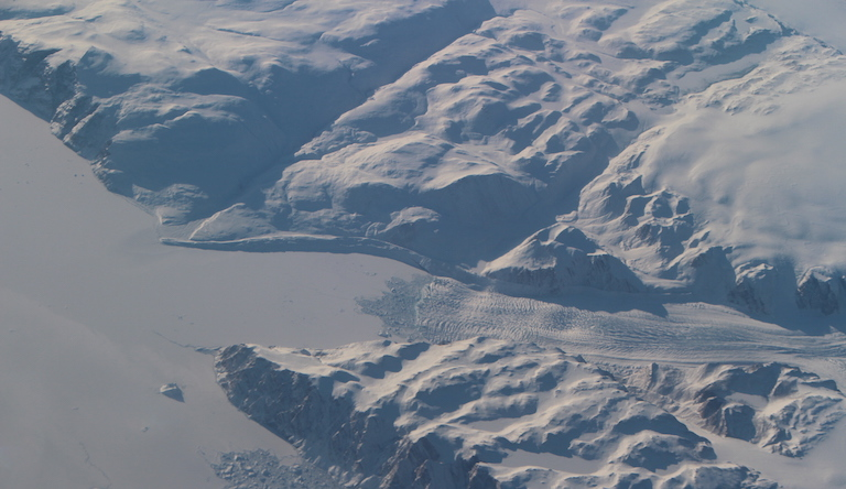 A glacier flows toward a frozen fjord on the Greenland coast, as seen from NASA's modified G-III aircraft. Credit: NASA/JPL