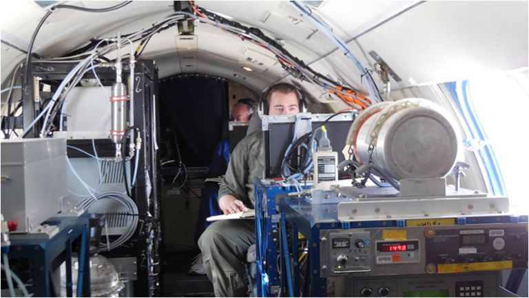 Inside one of three chase planes, NASA scientists Richard Moore and Bruce Anderson analyze exhaust from the DC-8 ahead.