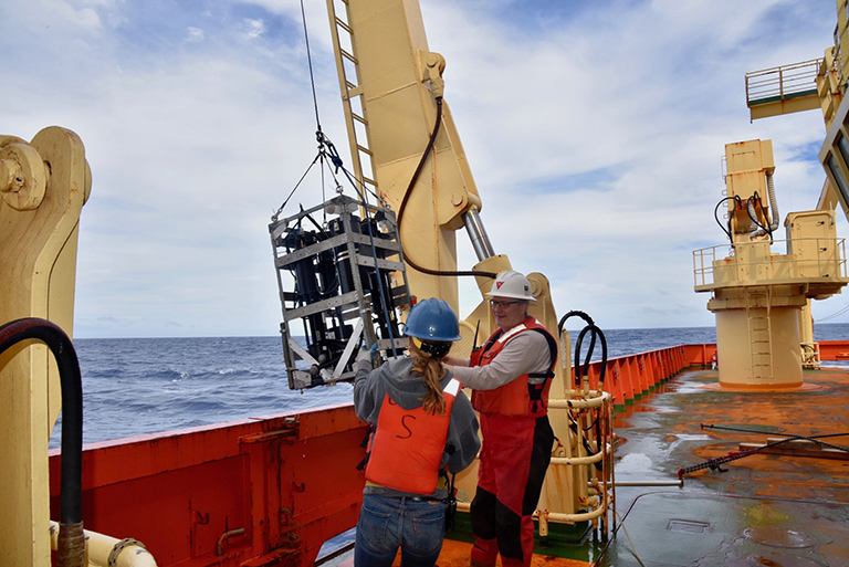 Crew members prepare an optical instrument for deployment over the side of the ship to collect optical measurements