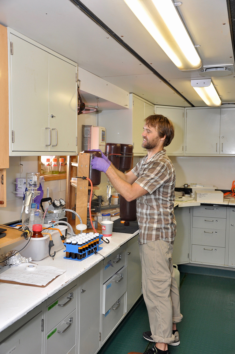 Mike Novack of NASA studies the optical and biological characteristics of sea water samples in the ship's laboratory.