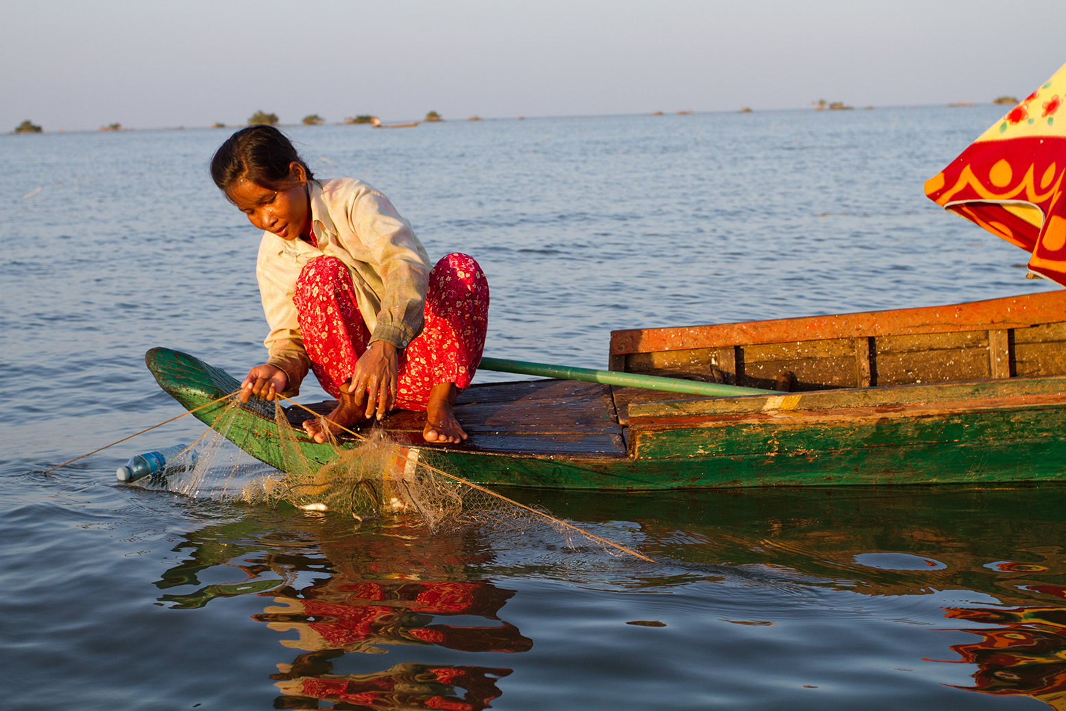 A person fishing at sunset on Tonlé Sap Lake, near Akal village in Cambodia.