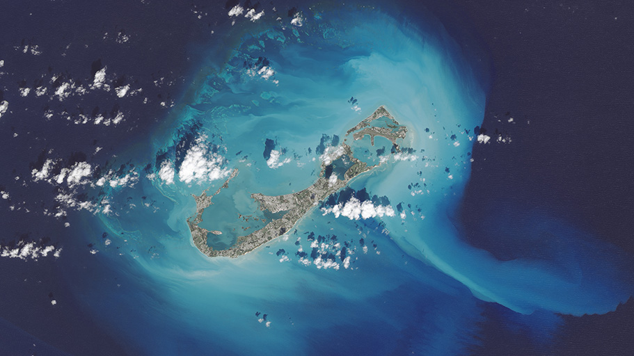 Light blue and white sediment is revealed around islands.