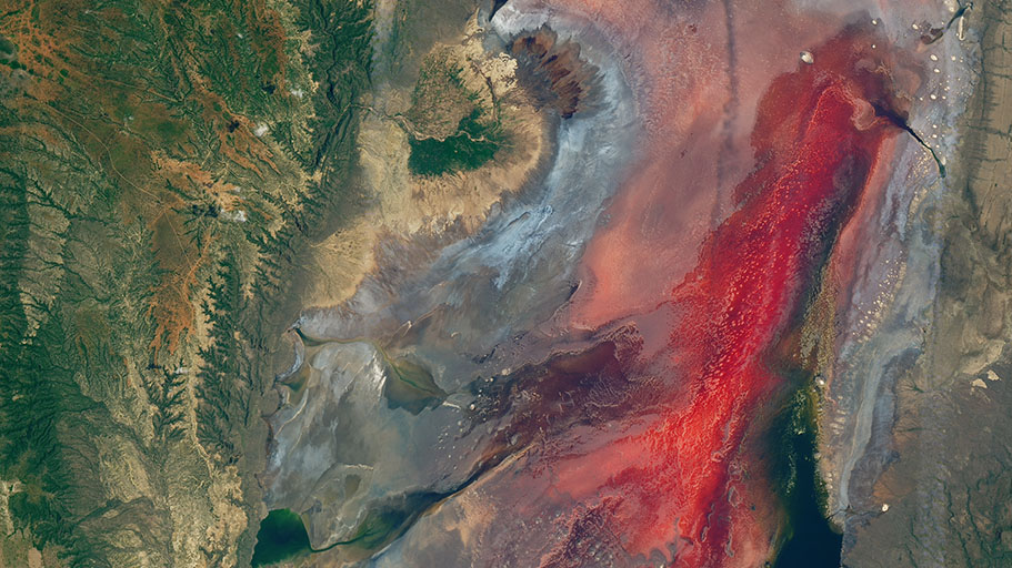 Brown, rocky land masses surround a red pool of water.