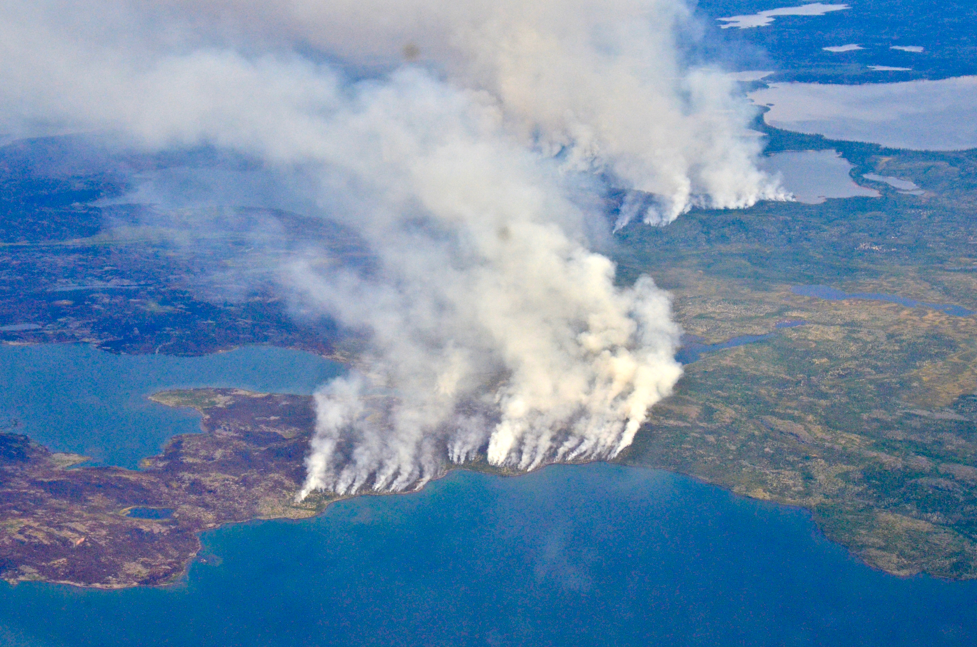 Large smoke plumes drift over land and ocean.