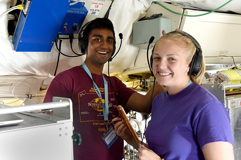 SARP participants Sujay Rajkumar and Kiersten Johnson on board the DC-8 operating Whole Air Sampling instrumentduring a science flight on June 26, 2018. Credit: NASA/Megan Schill