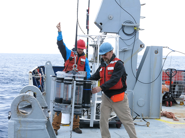 WHOI marine chemist Ken Buesseler (right) helps deploy a sediment trap from the research vessel Roger Revelle as part of the EXPORTS program.