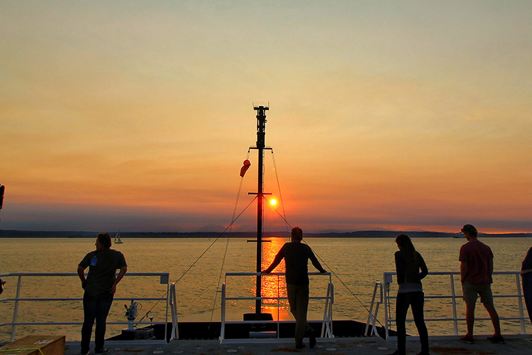 Scientists and crew aboard the Sally Ride watches the sunset as the ship leaves port in Seattle.