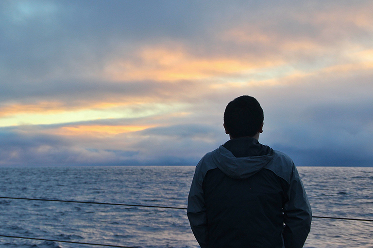 Yuanheng Xiong watches the sunrise from the back deck of the R/V Sally Ride.