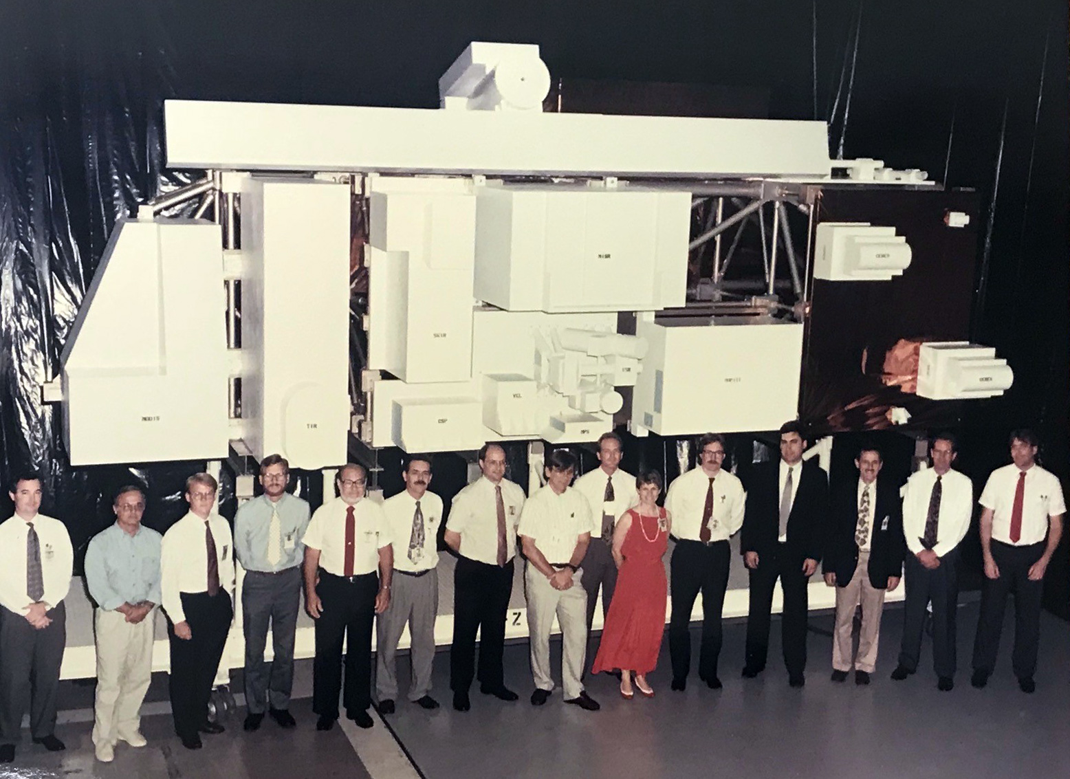 Members of the Terra design team stand in front of a true-to-size model of the satellite in the mid-1990s.