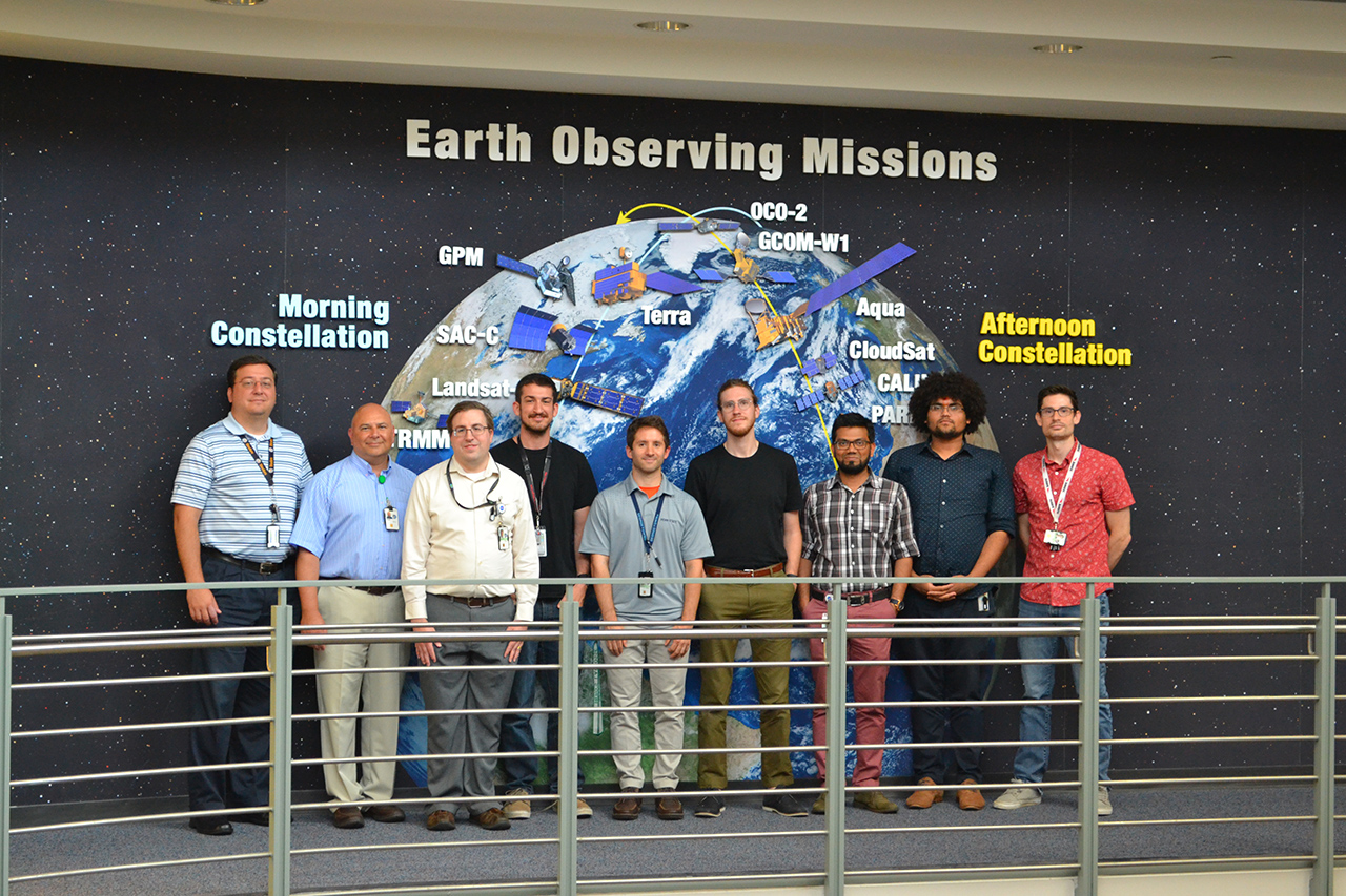 The offline Terra mission operations team stands in front of an image of the fleet of NASA Earth Observing Satellites.