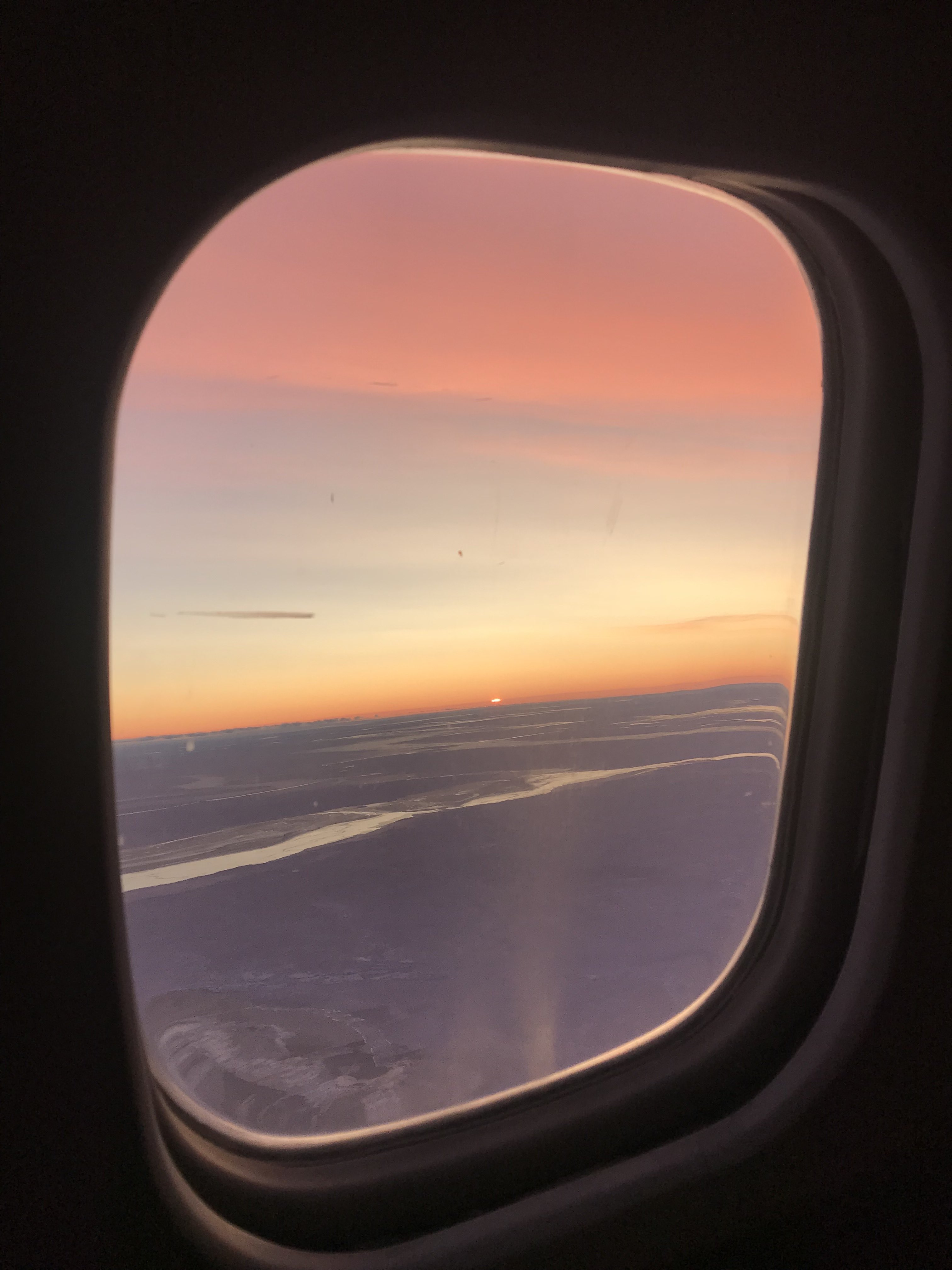 Sunrise over the Weddell Sea and sea ice below from the window of the DC-8