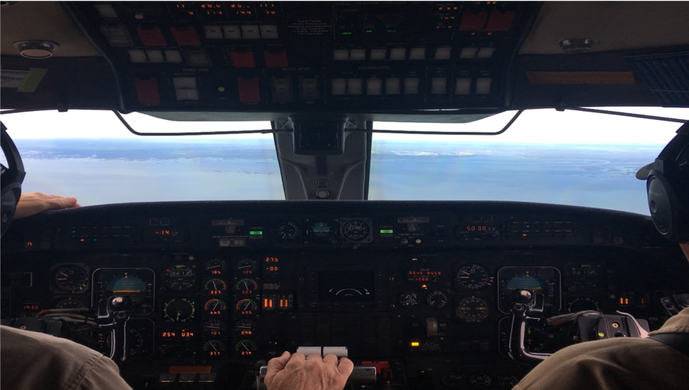 Mandy Bayha gets a pilot's view from the jump seat as the NASA Gulfstream III comes in for landing, the town of Yellowknife on the shores of Great Slave Lake in view.