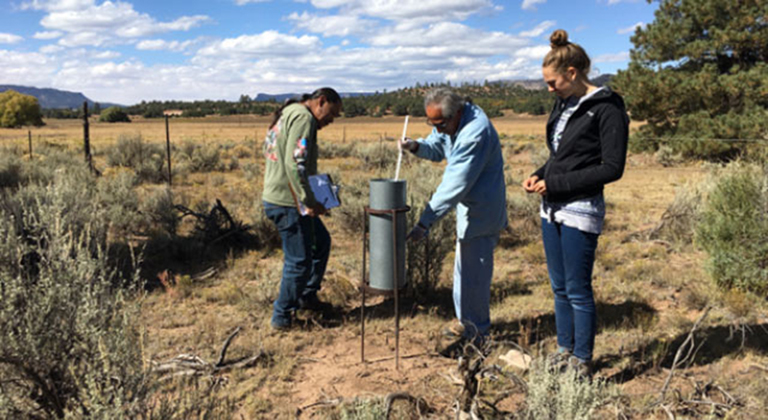 Ralphus Begay and Irving Brady, with the Navajo Nation Department of Water Resources, take monthly precipitation totals at a rain-gauge location.