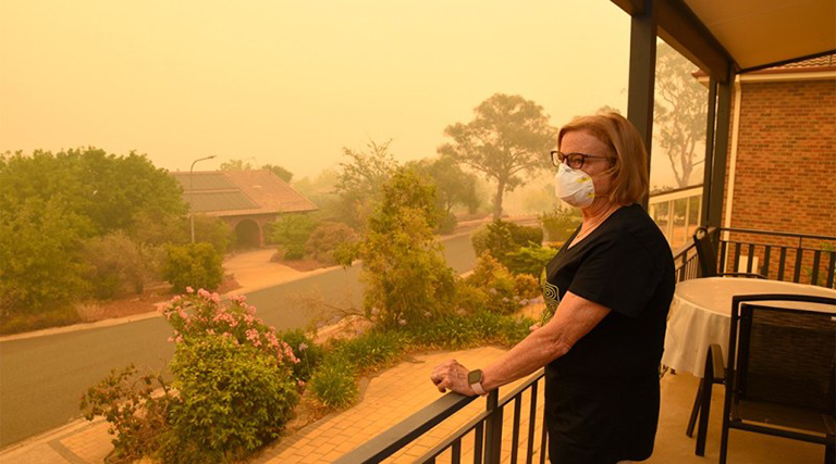 A woman on a balcony wears a face mask to protect herself against very dangerous levels of air pollution created by nearby wildfires.