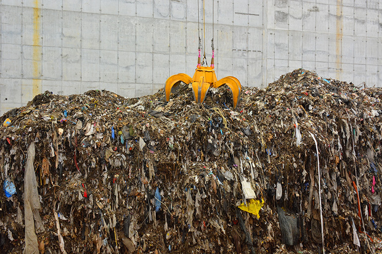A grapple moves a pile of garbage to the incinerator to be converted to energy in the renewable energy facility instead of being added to a landfill. Photo courtesy of Solid Waste Authority of Palm Beach County.