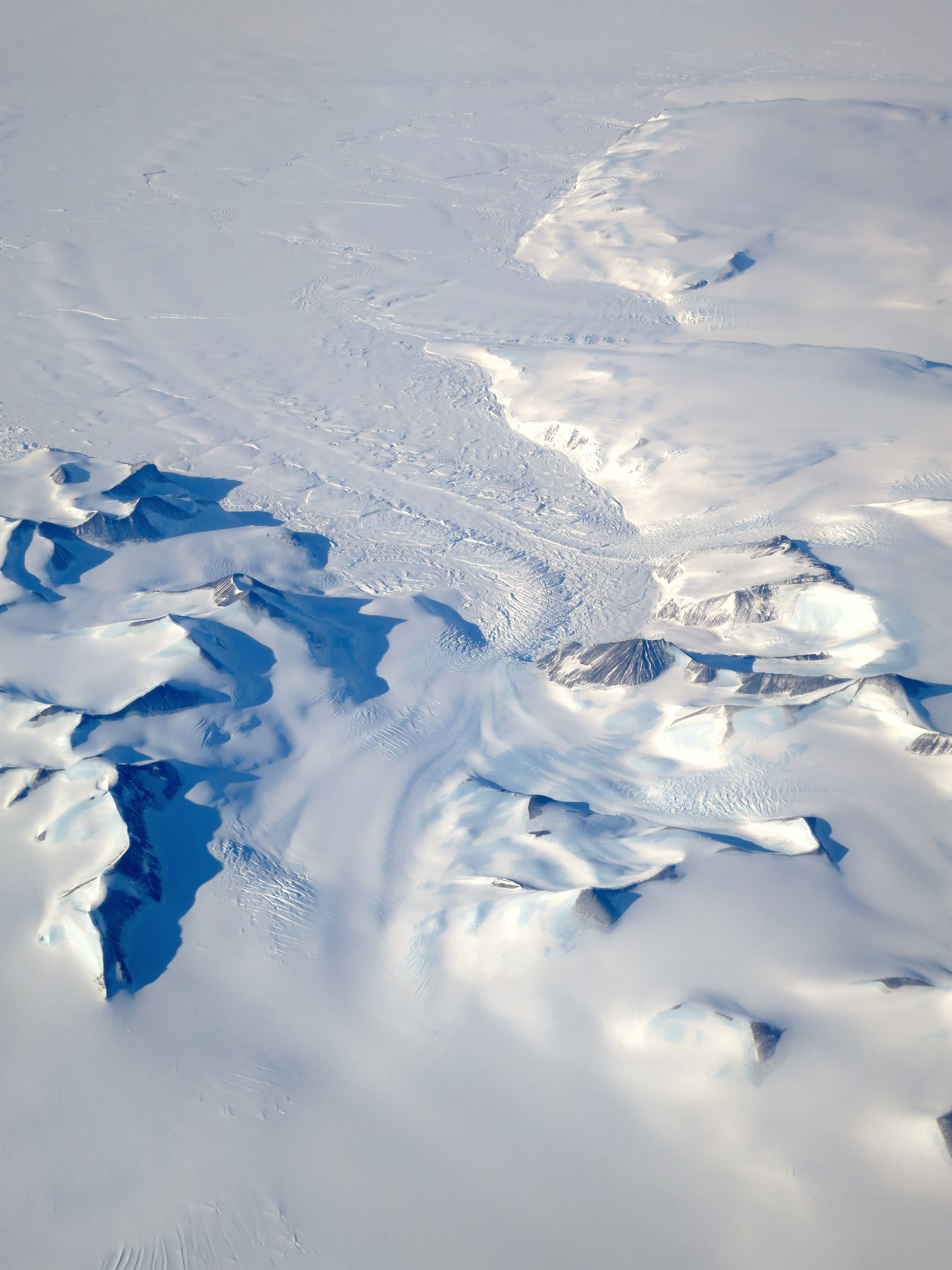 A glacier winds between peaks in the Antarctic Peninsula as seen on Oct. 3, 2015, from the NCAR G-V aircraft during Operation IceBridge's southern campaign. Credit: NASA/David Rabine.