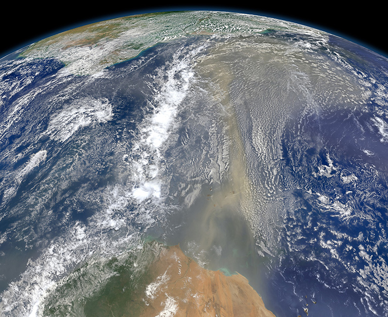 Satellites have documented that human-produced and natural air pollution can travel a long way. This 2014 NASA satellite image shows a long river of dust from western Africa (bottom of image) push across the Atlantic Ocean. Credit: NASA.
