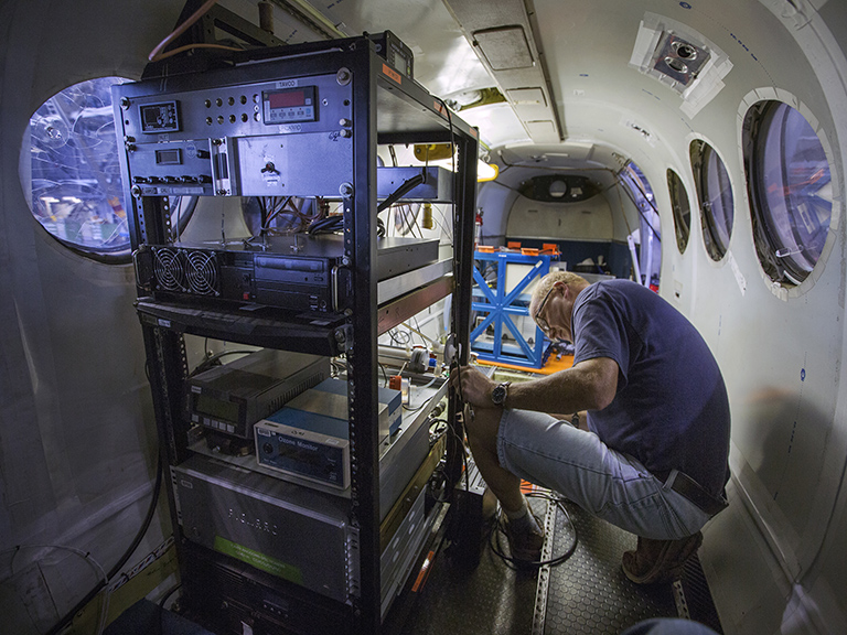 Technician Jim Plant checks an instrument rack aboard the King Air B-200 at NASA's Langley Research Center in Hampton, Virginia, in preparation for the first ACT-America flights this month.