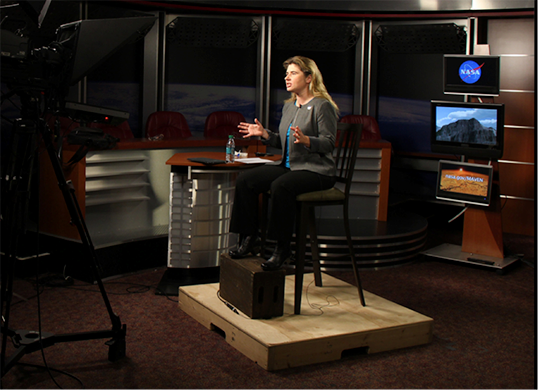 Alone on the set, Michelle Thaller of NASA's Goddard Space Flight Center communicates through the camera lens to a TV station audience she can't see.