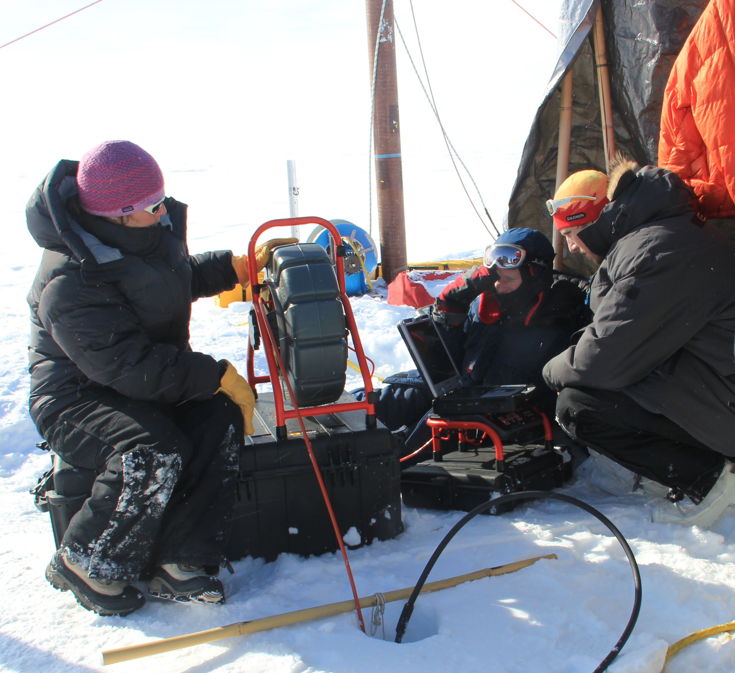 Glaciologist Lora Koenig (left) operates a video recorder that has been lowered into the bore hole to observe the ice structure of the aquifer in April 2013.