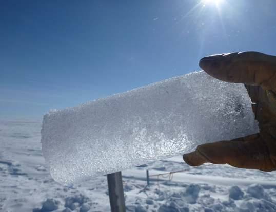 An ice core segment extracted from the aquifer, with trapped water collecting at the lower left of the core. Credit: NASA's Goddard Space Flight Center/Ludovic Brucker.