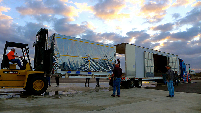 The transportation canister containing NASA's Soil Moisture Active Passive (SMAP) spacecraft is offloaded from the truck that delivered it from NASA's Jet Propulsion Laboratory in Pasadena, California, to the Astrotech payload processing facility on Vandenberg Air Force Base in California. Credit: NASA/JPL-Caltech