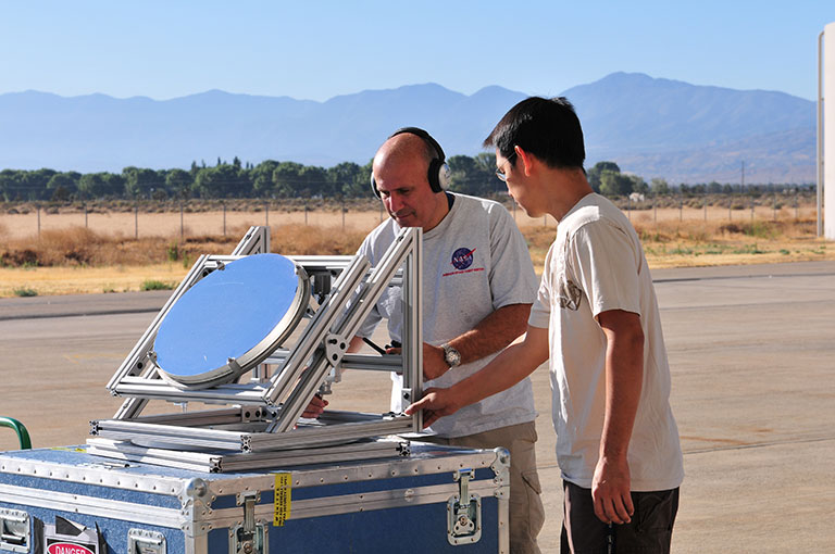Principal Investigator Haris Riris (left) and Stewart Wu prepare a prototype of the methane sounder (the mirror is an alignment tool) before demonstrating it aboard NASA's DC-8 research aircraft in 2011. Another flight is scheduled for later this year. Credit: Emily Schaller. View a larger image.
