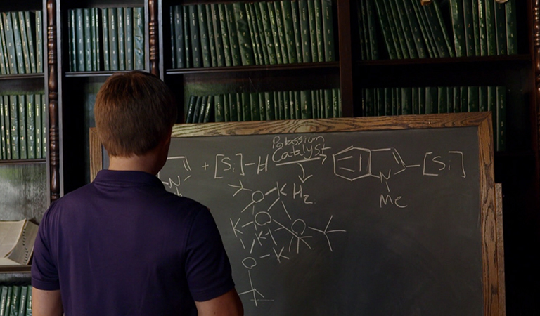 Anton Toutov, Caltech grad student and discoverer of a renewable catalyst, immersed in chemical formulas on a chalkboard. Credit: Caltech Resnick Institute.