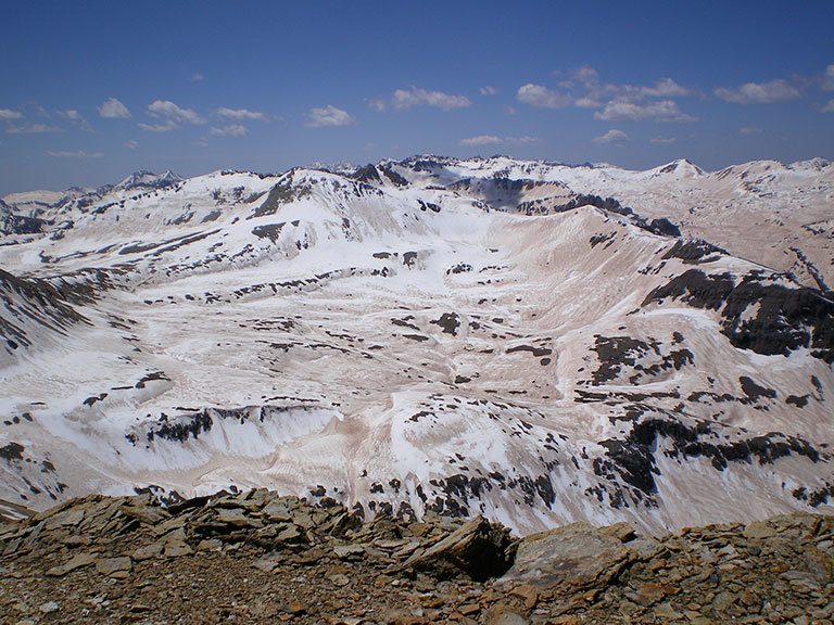 A photograph of the extreme dust deposition from the deserts of the Colorado Plateau onto the Colorado Rockies snowpack in 2009. Taken from the high point of the Senator Beck Basin in the San Juan Mountains, it captures the extent of the impact of darkening in which the snow albedo dropped to about 30%, more than doubling the absorption of sunlight. Credit: S. McKenzie Skiles, Snow Optics Laboratory, NASA/JPL. View larger image.