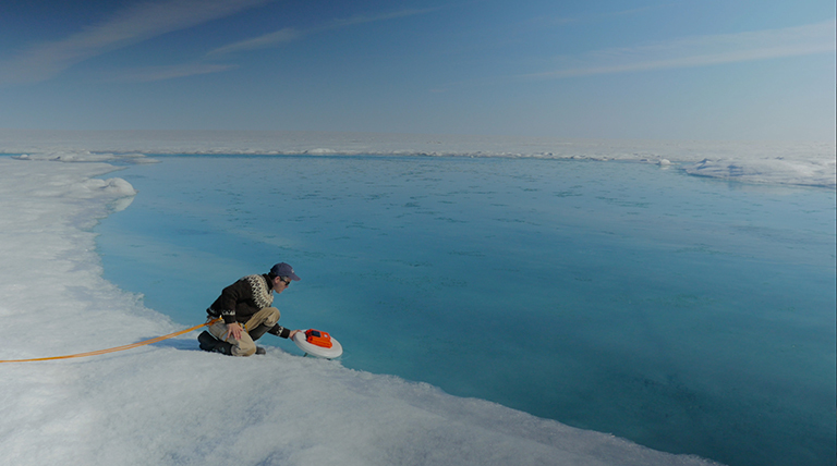 Laurence Smith (University of California, Los Angeles) deploys an autonomous drift boat equipped with several sensors in a meltwater river on the Greenland ice sheet. Credit: NASA's Goddard Space Flight Center/Jefferson Beck