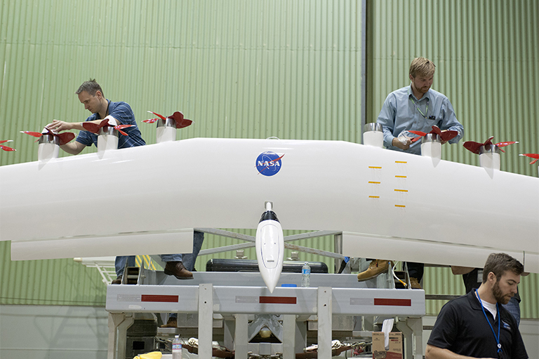 Engineers work on a wing with electric motors that is part of an integrated experimental testbed. From left are Sean Clarke, left, Kurt Papathakis at upper right and Anthony Cash in the foreground. Credit: NASA Photo/Tom Tschida.