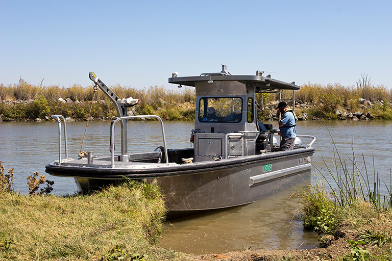 The USGS R/V Mary Landsteiner shown at a brief stop during a study in the Northern San Francisco estuary. USGS scientist Bryan Downing is shown calibrating the on-board real-time underway measurement system. Credit: Stephen de Ropp, de Ropp Media.