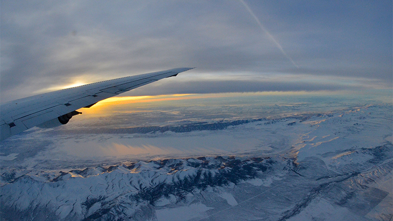 A view looking out over the plane's wing and a dim sun shining on snow-covered mountains.