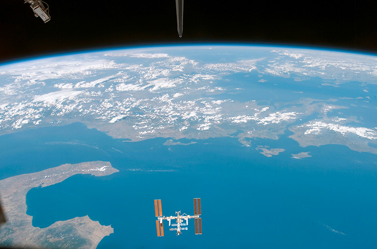 The view of the International Space Station orbiting Earth as seen from Space Shuttle Endeavour.