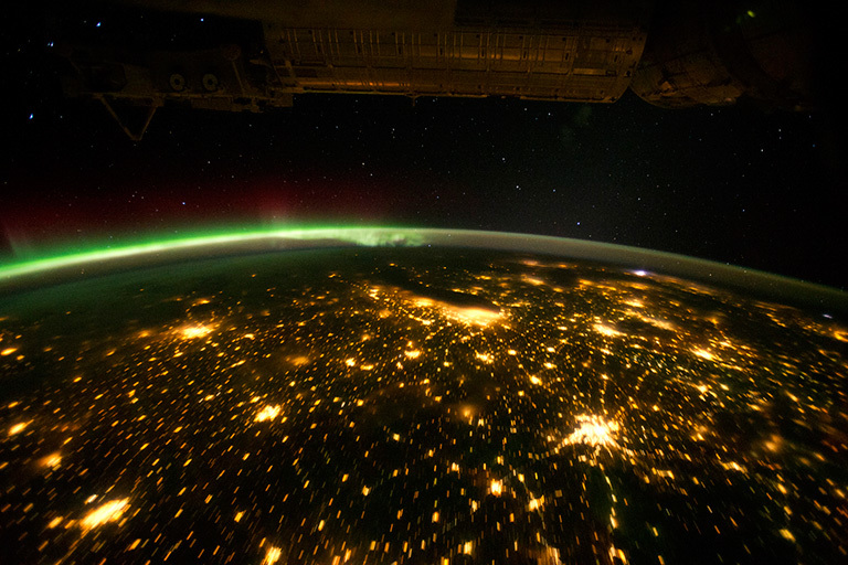 The Midwestern United States illuminated by a patchwork quilt of light as seen from the International Space Station (ISS). The aurora borealis also shines brightly in this view.
