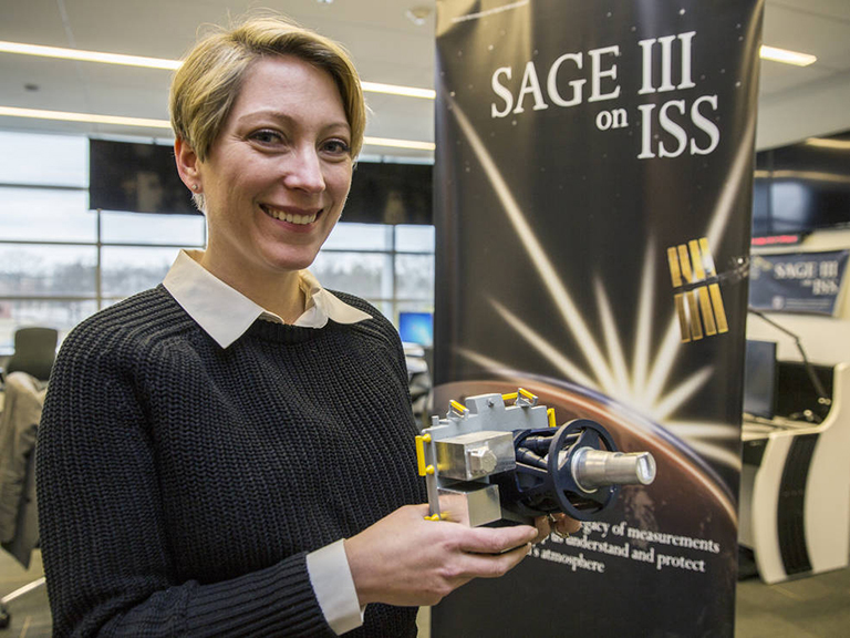 Brooke Thornton, of NASA's Langley Research Center in Hampton, Virginia, is the mission operations manager for SAGE III on the International Space Station. She is holding a scaled model of the instrument. Credit: NASA/David C. Bowman.
