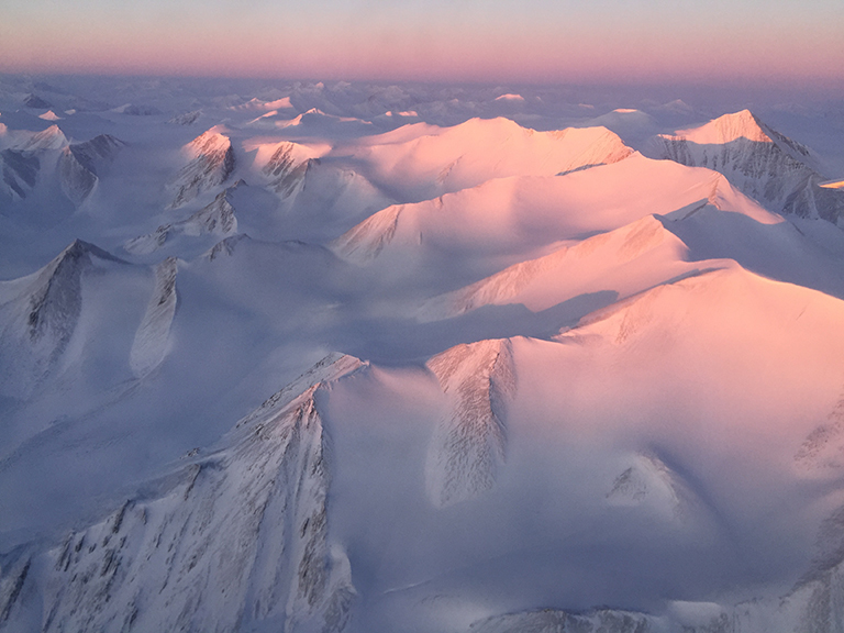 Ellesmere Island mountain tops bathed in light as the sun began to peak over the horizon during Operation IceBridge's first flight of its 2017 Arctic campaign, on March 9, 2017. Credit: NASA/Nathan Kurtz.