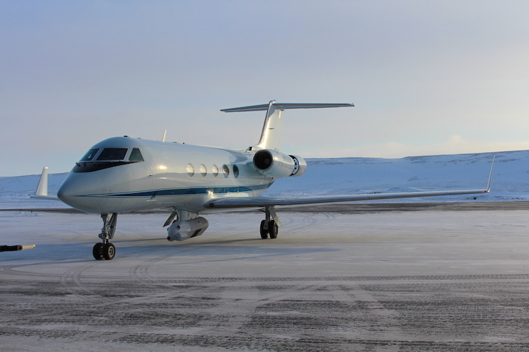 NASA's modified G-III aircraft, with the GLISTIN-A radar instrument visible below, on the runway at Thule Air Base, Greenland.