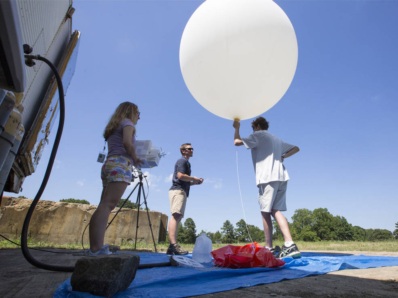NASA Goddard post-doctoral fellow John Sullivan, center, along with interns Lindsay Rodeo, left, and Lance Nino, prepare to launch a balloon that will take ozone measurements in the skies over southeastern Virginia.