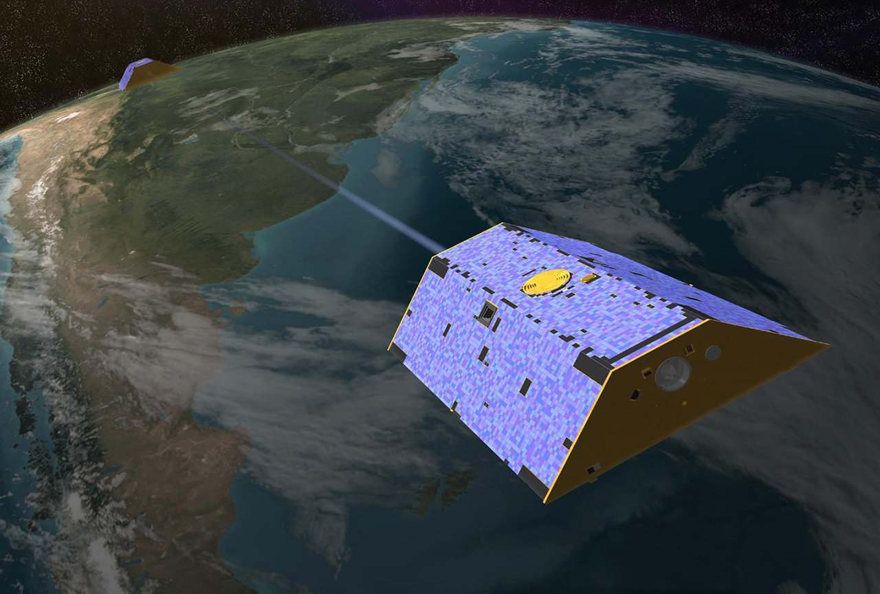 An artist's rendering of the twin GRACE satellites in orbit over Earth.