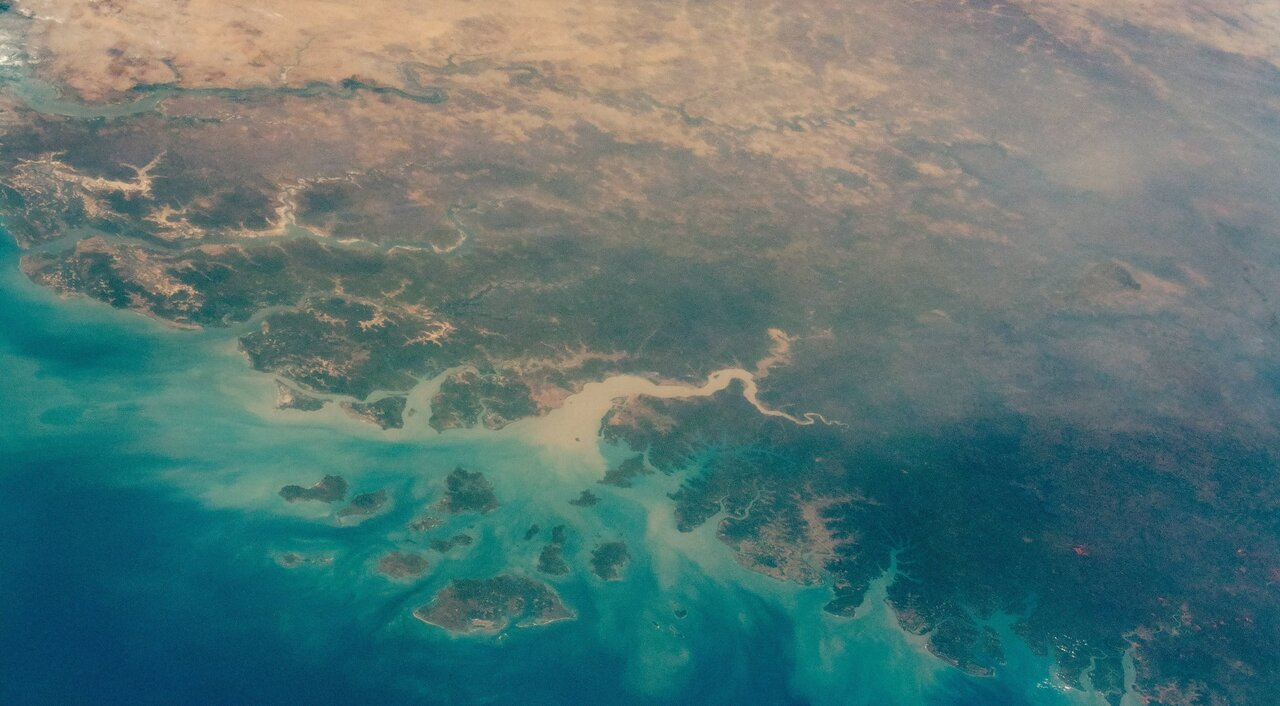 Photo of West African coast from space, showing turquoise water, green coastal areas and tan desert.