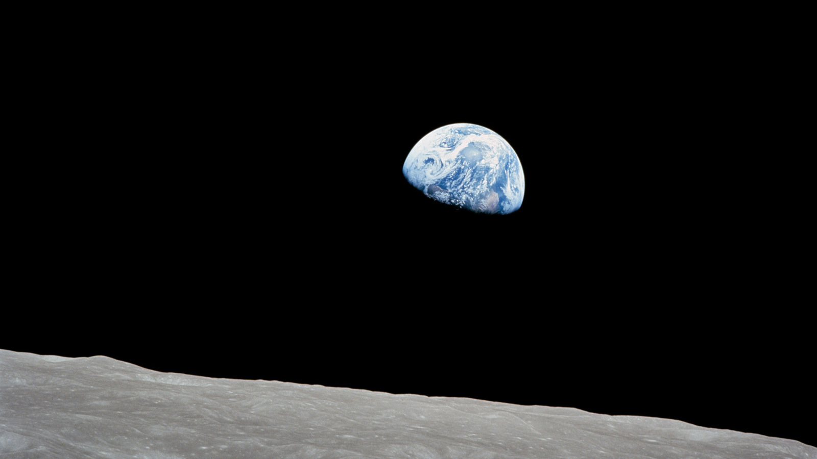 The Earth rises above the lunar horizon in this telephoto view taken from the Apollo 8 spacecraft