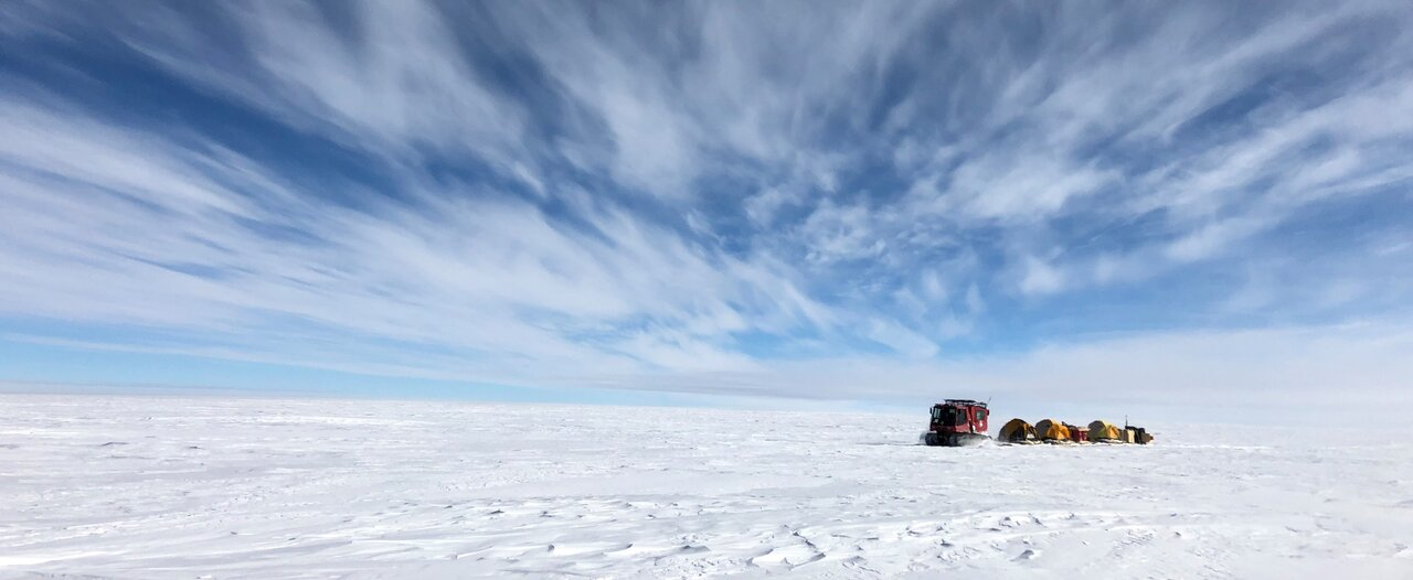 Wide-angle shot of research camp under blue sky in Antarctica