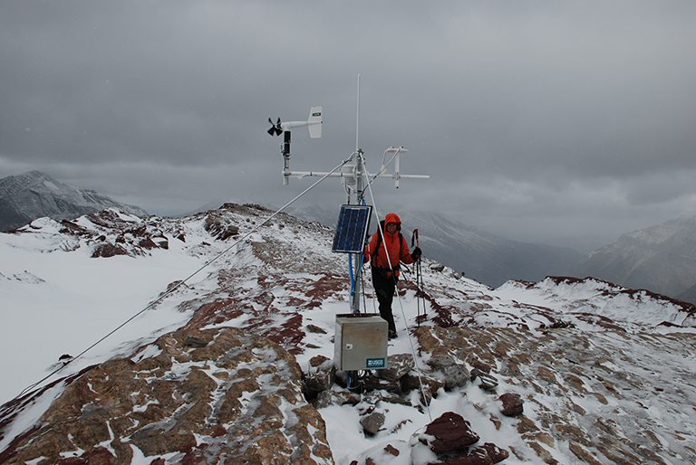 Weather stations are set up throughout Glacier National Park in Montana to monitor and collect weather data. These stations must be visited periodically for maintenance and to add or remove new research devices. Credit: GlacierNPS, CC BY 2.0, via Wikimedia Commons